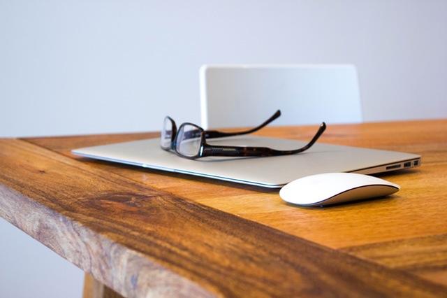 gafas y laptop sobre la mesa de la oficina en una empresa con seguro nuevo