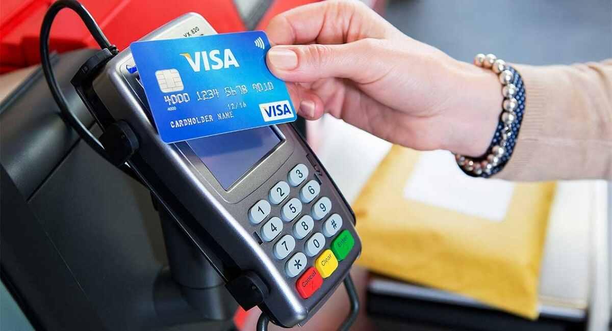 Una persona realiza un pago con tarjeta de crédito en un lector de tarjetas de crédito